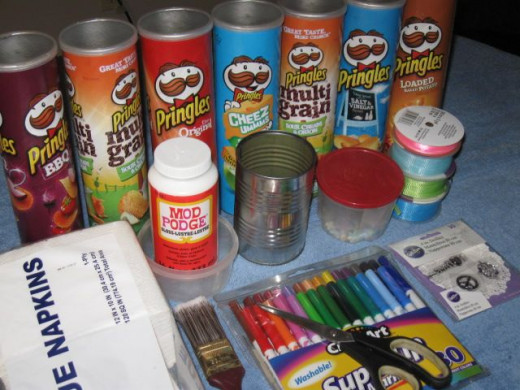 Materials:  1 regular can, 5 Pringles potato chip cans, Mod Podge, paper napkins, markers, ribbon, pony beads, brads, tape and five large beads.