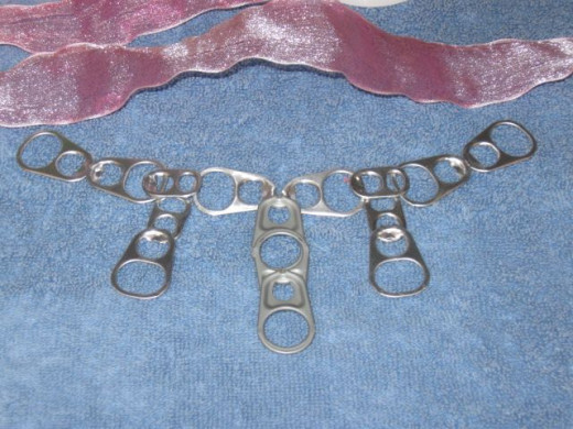 Start by laying out your pop tabs. I used eight large ones and two small ones. Lay them out as you see here, minus the two hanging down on the sides. We will begin by connecting two at a time across the top. As you can see from the finished choker, I