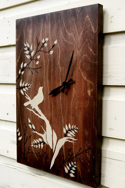 This pretty clock has a stencilled and embroidered bird design on the front.