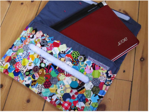 Loads of mini hexagons sewn together on dark grey fabric and made into a lovely laptop cover.