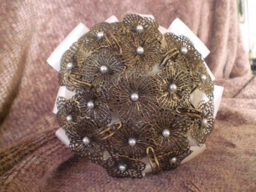 This is a brooch bouquet made from repurposed bronze pins made by AlwaysAfton on Etsy. See the link below.