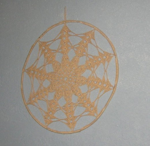 A lace doily was sewn to a circular wire. This looks great on the wall (as shown) or in a window.