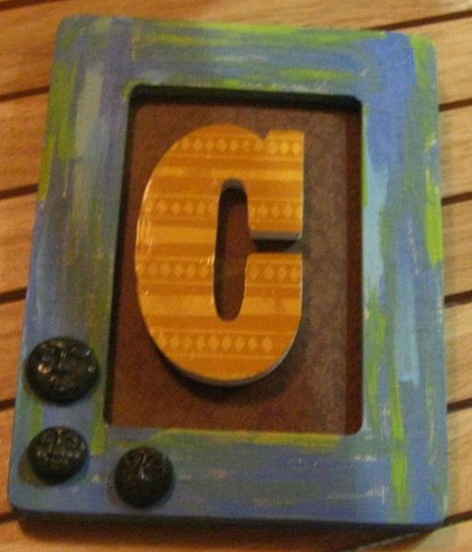 Give me a C! Framed art collage using a painted frame, scrap book paper covered letter, and three polymer clay faces.