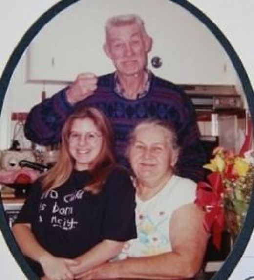 Grandpa and grandma and granddaughter smiling for the camera.