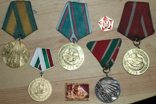 A selection of Bulgarian medals together with two Russian badges