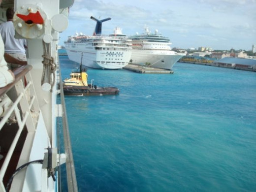 A little tugboat pushing a big cruise ship in Nassau Harbor.
