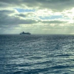 A ship out at sea, just after daybreak