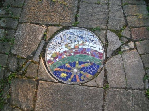 This is one of several tile work plaques set into the crazy paving. It uses recycles pottery to make a mozaic and is both pretty and interesting.