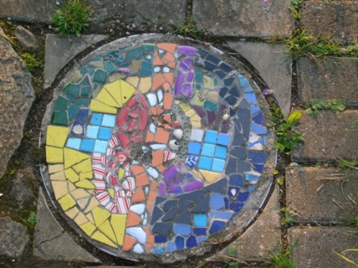 Here is yet another attractive plaque set into the crazy paving. It gives a real Gaudi feel to the grotto which we love! These mosaics were produced by a group of artists with learning difficulties. The group is run by Phil Robinson and the artists n