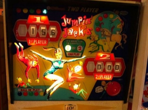 A pinball game before a digital scoreboard feature women dressed as bunnies and elf like creatures.