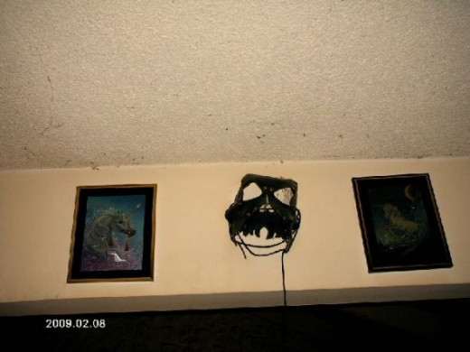 An exorcist's mask and two unicorn pictures.