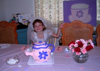 "Here's the birthday girl.  Her choice of dress up was a wedding gown.  You can see the tea cup from the ""Pin the tea bag on the Tea Cup"" game in the background.  Of course fresh flowers made a wonderful addition to the decorations."