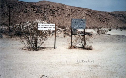 Pegleg Smith Monument in Borrego Springs. If you seek gold in the desert, add a rock to the pile behind the sign.