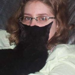 Woman Holding Black Cat to Face