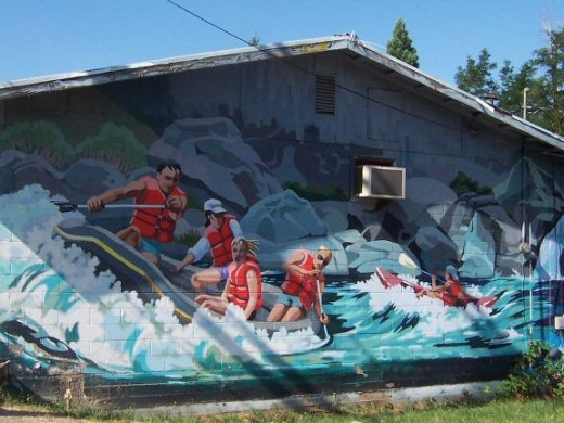 A rafting mural on the end wall of the old hardware store.