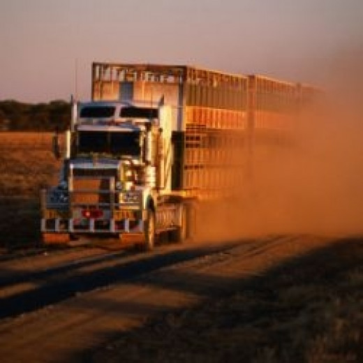 Art     Artists     Artists by Name     L     Holger Leue Road Train Driving along Dusty Road, Kynuna, Australia