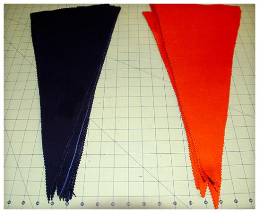 One set of orange pennants and one set of black pennants ready to be hemmed.
