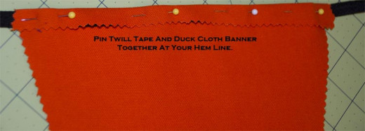 Lay your twill tape underneath your hem line. Pin the tape and duck cloth together to prepare for your hem stitch.