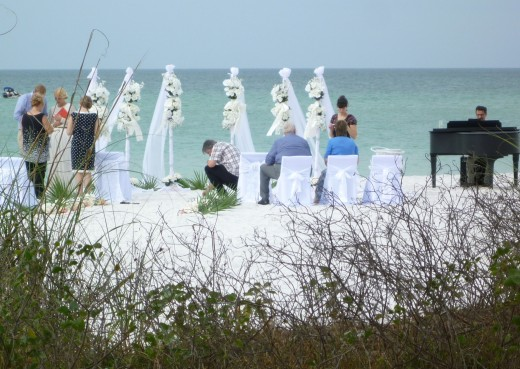 Guests mingle after an intimate beachside wedding on Bradenton Beach