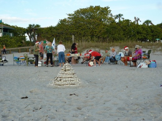 A family celebrates their Yuletide holiday with a beachside picnic, complete with a sandy Christmas tree.