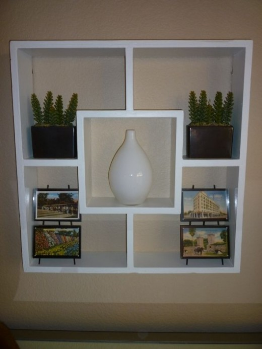 A close up of the large shadow box wall feature in the master bedroom.  The white vase in the center of the shadowbox came from Goodwill.
