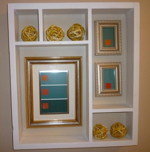 I filled it with some yellow rattan orbs and three picture frames, filled with paint chip art.  I purchased the two small picture frames for $1 apiece at a local consignment store.