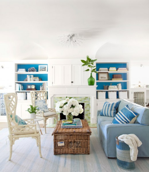 Hues of blue with white are used with a rattan chair and antique wicker trunk.