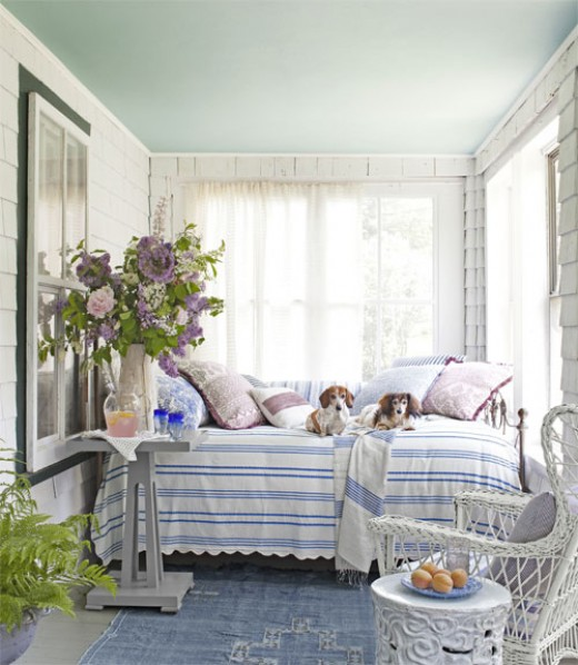 Striped pastel blue & white cover daybed nestled on the back porch. Oversized mauve flowers & vase fit perfectly.  White furniture & cloth blue rug.
