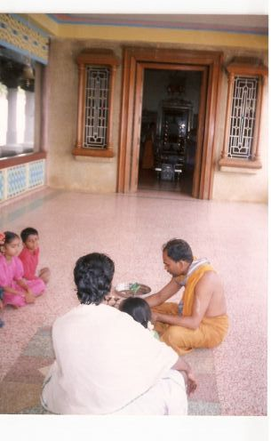 Infront of the family goddess,on mama's lap priest is seen