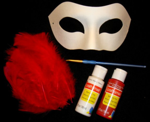 Supplies to make a fox mask: feathers, mask, paint and brushCopyright c Kirsti A. Dyer.