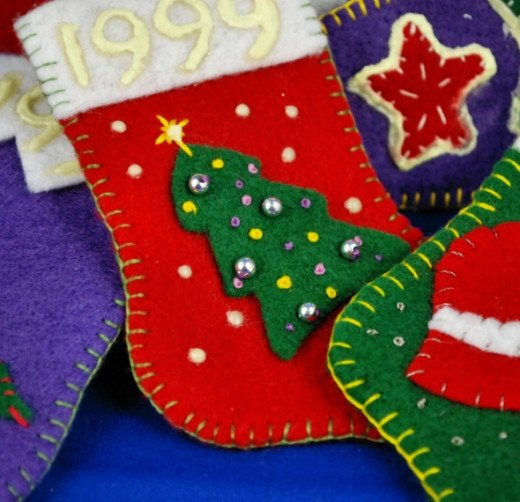 "The Christmas tree is decorated with beads and French knots, and surrounded by glow in the dark ""stars.""The star shapes on the stocking in the background were stitched and decorated in place, then edged with glow in the dark paint."