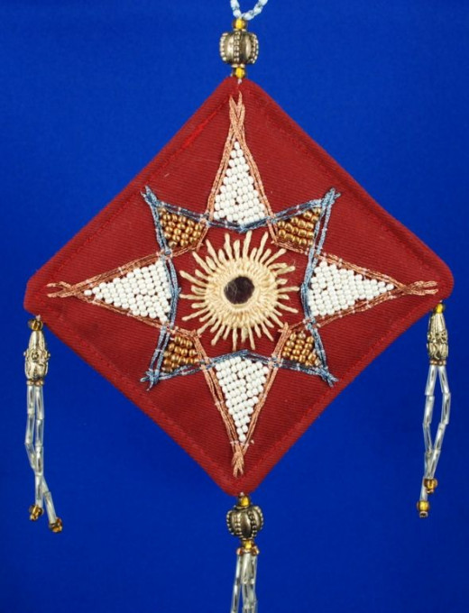 "All the shisha mirrors were stitched into place with rayon embroidery thread - a very slippery medium!This decoration also used metalling embroidery thread, metallic and ""pearl"" seed beads, and the fringes are made of bugles topped with metal beads"