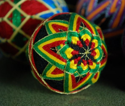 This was one of the first temari I ever made, worked on a 2 inch core.  A pattern with two centres, one at each pole, each is made up of a pair of overlapping 4 point stars.