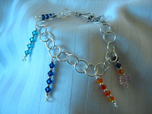 Bright colors, moving elements and shine all come in to play with this fun bracelet.