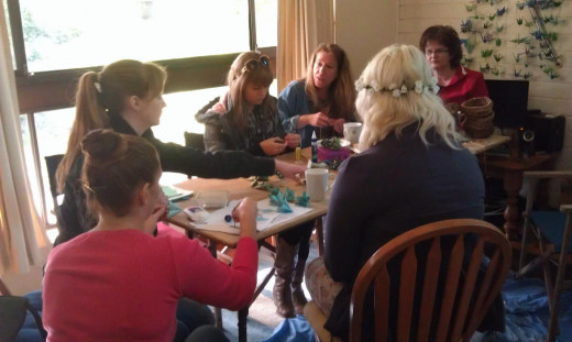 Friends and family chatting and working around the craft table at one of our crafternoons.