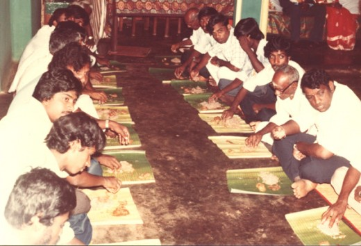 Those who present during the wedding are sitting on the floor and having lunch on banana leaves.