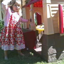 My granddaughter by her outdoor playhouse.
