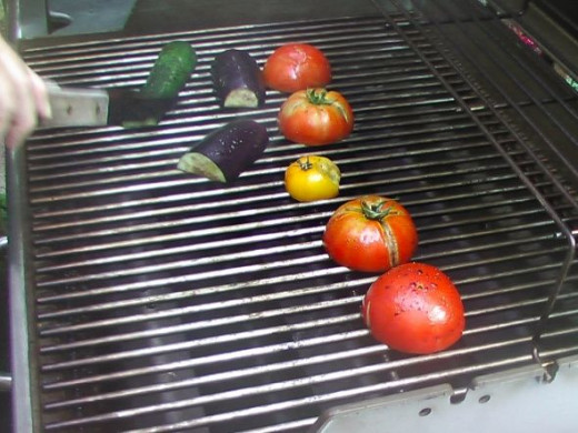 Using tongs to place the veggies on the gas Weber grill.