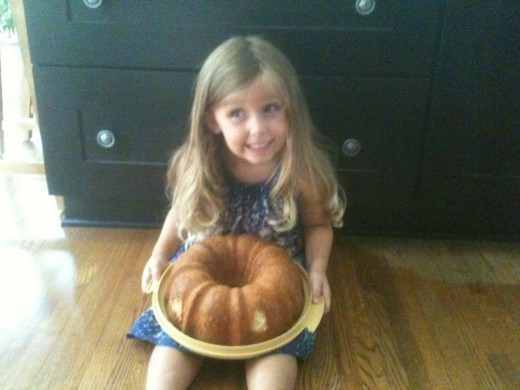 Beautiful child with her pound cake out of the pan.